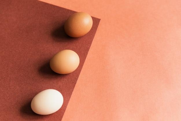 Trois œufs de poule sont pondus sur du papier de couleurs naturelles. la texture du papier et de l'œuf est beige. lignes et triangles. oeufs de pâques.