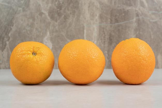 Trois oranges entières sur table grise