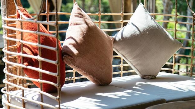 Trois oreillers placés sur une chaise avec le soleil, intérieur