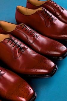 Trois paires de chaussures brogues dans un cercle, chaussures oxford marron sur fond bleu, vue de dessus, copiez l'espace.