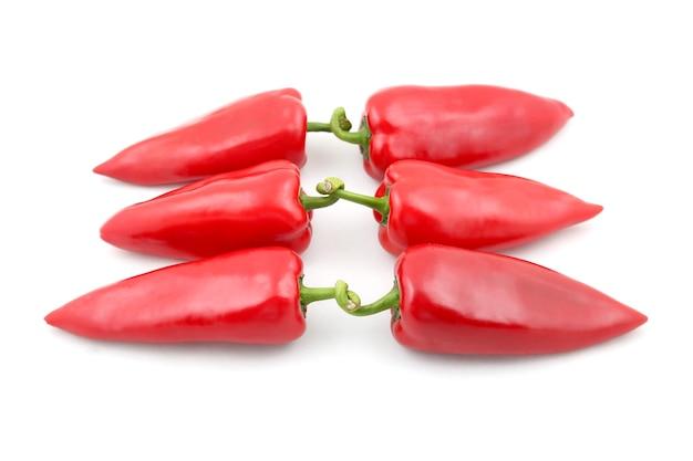 Trois paires de poivrons rouges sur une surface blanche