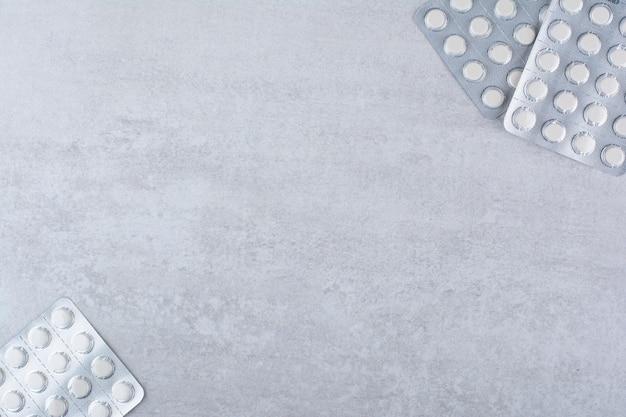 Trois paquets de médicaments sur une surface en marbre.