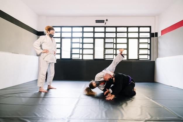 Trois partenaires dans une formation d'arts martiaux avec des kimonos pratiquant des techniques sur le tapis de gymnastique portant tous des masques faciaux en raison du covid 19