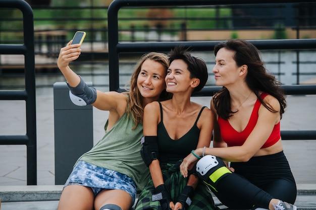 Trois patineuses souriantes prenant un selfie, s'appuyant sur la balustrade du skatepark.. assis près les uns des autres, regardant la caméra du téléphone.