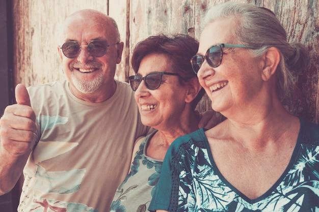 Trois personnes âgées debout contre une porte en bois souriant joyeusement - concept de retraité senior pendant les vacances