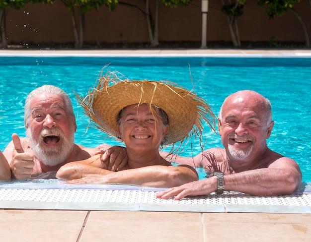 Trois personnes âgées heureuses s'amusant dans la piscine sous le soleil - deux frères, expression faciale, sourires et rires