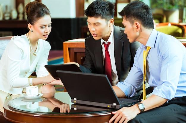 Trois personnes de bureau chinois asiatiques ou hommes d'affaires et femme d'affaires ayant une réunion d'affaires dans un hall de l'hôtel discuter de documents sur une tablette tout en buvant du café