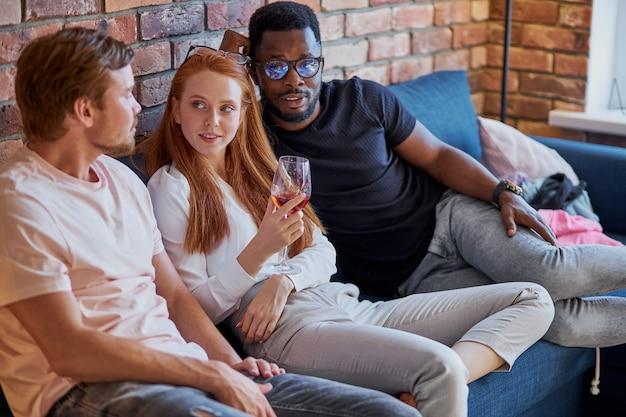 Trois personnes diverses appréciant passer du temps à la maison