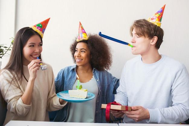 Trois personnes fêtent leur anniversaire. ils portent des chapeaux drôles. la fille tient une assiette avec un gâteau pendant que le gars a un cadeau dans ses mains et une chose étrange dans sa bouche.