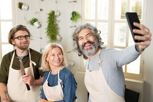 Trois personnes joyeuses en tabliers regardant la caméra d'un smartphone tout en faisant un selfie ou en enregistrant une vidéo d'un cours de cuisine ou d'une classe de maître