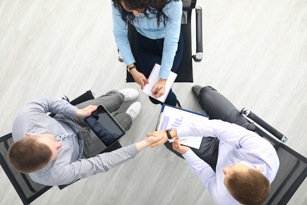 Trois personnes s'assoient sur une chaise en vue de dessus du cercle et discutent du travail.