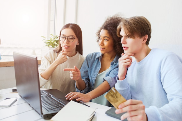 Trois personnes sont étonnées. ils regardent l'écran des ordinateurs portables. guy tient une carte de crédit.