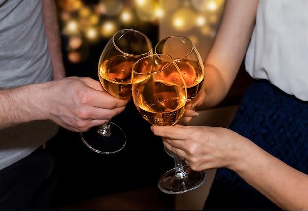Trois personnes trinquent des verres de vin