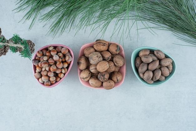 Trois petite assiette pleine de noix avec des pommes de pin de noël sur fond de marbre. photo de haute qualité