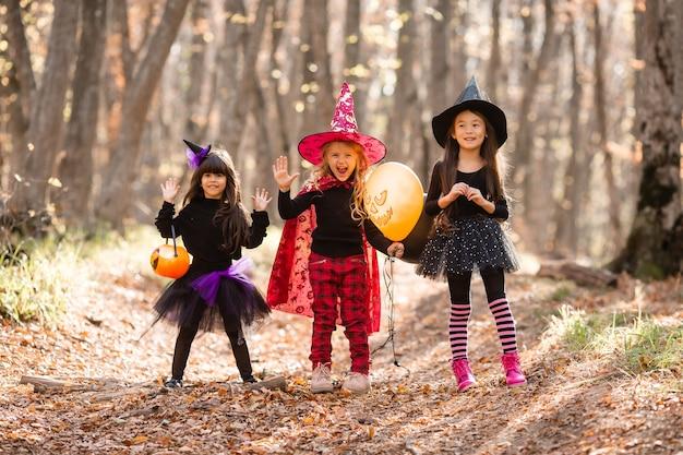 Trois petites filles en costumes de sorcière rient évoquent une promenade à travers la forêt d'automne