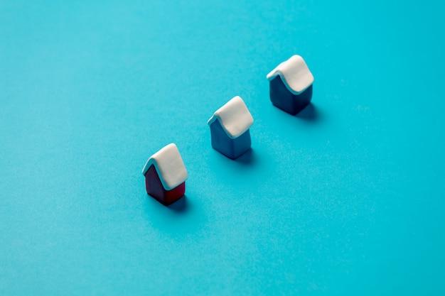 Trois petites maisons de jouets de noël sur une surface bleue