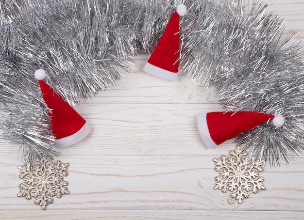 Trois petits chapeaux de père noël, flocons de neige et guirlandes d'argent