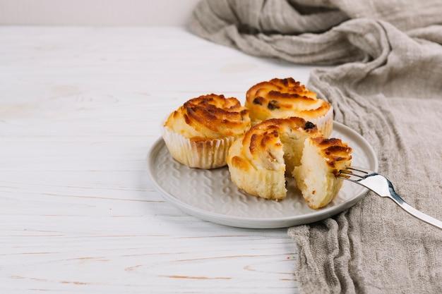 Trois petits gâteaux sur une assiette avec une fourchette sur un fond en bois