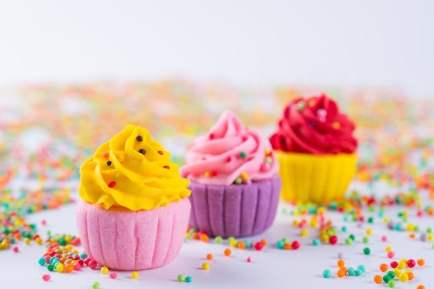 Trois petits gâteaux au sucre multicolores miniatures sur fond clair avec des paillettes