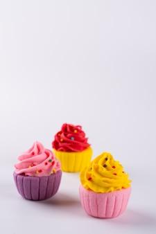 Trois petits gâteaux au sucre multicolores miniatures sur fond clair