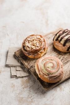 Trois petits pains au cinabon sur une planche en bois avec une serviette sur un fond clair. chignon classique américain.