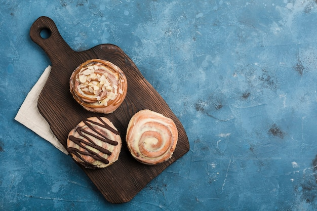 Trois petits pains au cinabon sur une planche en bois sombre avec une serviette sur un fond bleu. chignon classique américain.