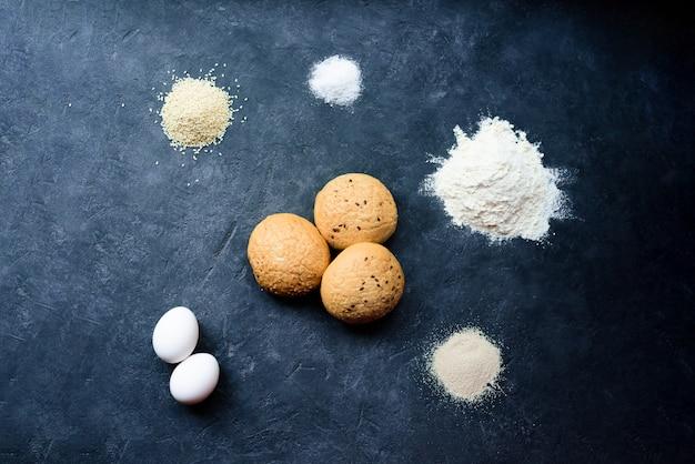 Trois petits pains au sésame au centre sur un fond sombre