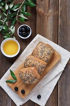 Trois petits pains de céréales fraîches sur une planche à découper en bois, huile d'olive, olives et feuilles d'olivier.