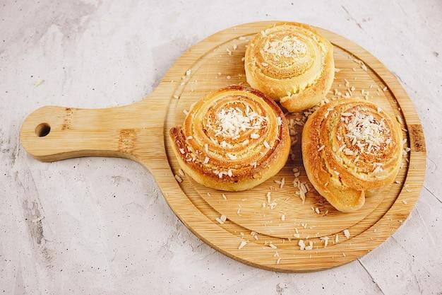 Trois petits pains sucrés faits maison à la noix de coco, photographiés d'en haut sur une planche en bois, fond gris béton (mise au point sélective). rouleaux de noix de coco sous forme de rouleaux. sans personnes.