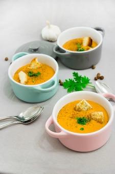 Trois petits pots ou bols avec une soupe à la crème à base de lentilles rouges avec des biscottes