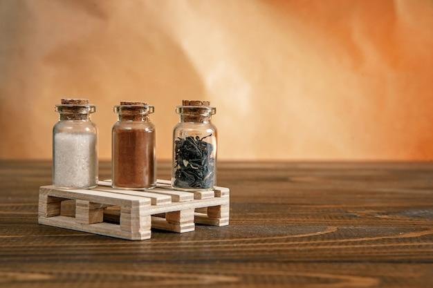 Trois petits pots remplis de sucre, de cannelle et de thé sur un support en bois sur la table