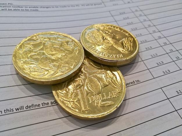 Trois pièces d'or de dollars australiens sur la feuille de facture