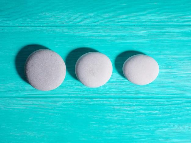 Trois pierres zen blanches d'affilée en ligne sur fond bleu.