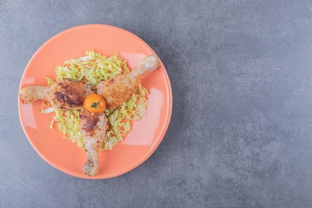 Trois pilons de poulet sur plaque orange.