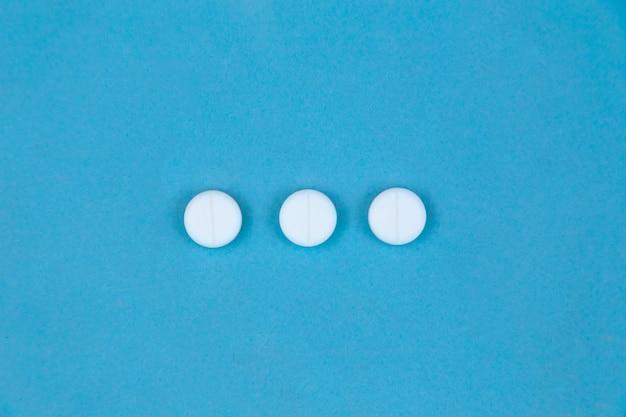 Trois pilules rondes blanches sur fond bleu. concept de communication de soins de santé et de médecine.