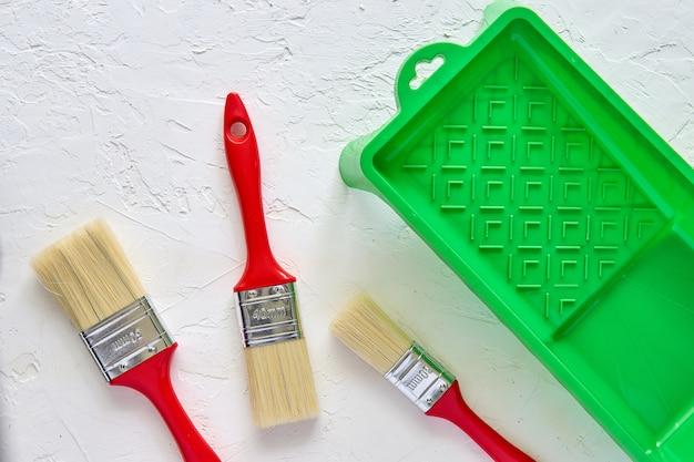 Trois pinceaux avec poignées rouges et bac à peinture verte sur fond de béton blanc. outils et accessoires pour la rénovation domiciliaire. vue de dessus