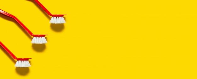 Trois pinceaux rouges se trouvent sur un jaune vif. dans le style du pop art.