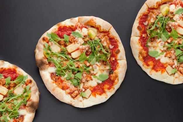 Trois pizzas au jambon fumé et roquette sur fond noir. savoureuse pizza italienne fine avec de la viande sur un sol sombre-vue de dessus à plat