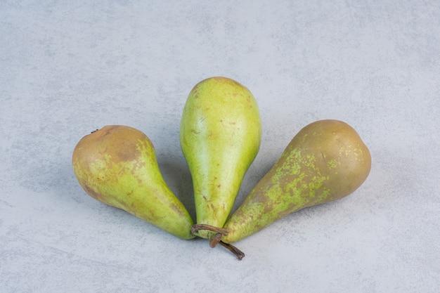 Trois poires fraîches sur fond gris.