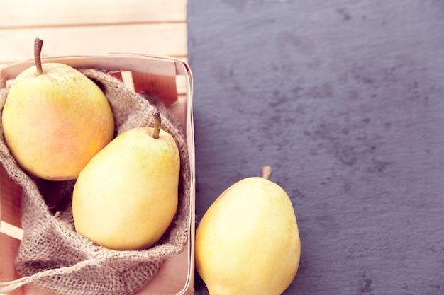 Trois poires jaunes sur un fond en bois et noir