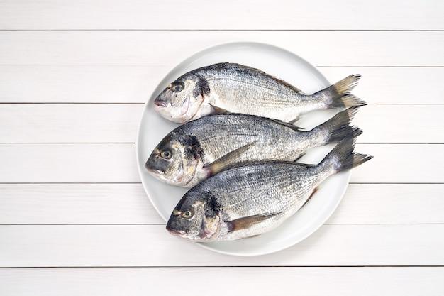 Trois poissons crus dorado frais sur une plaque blanche.
