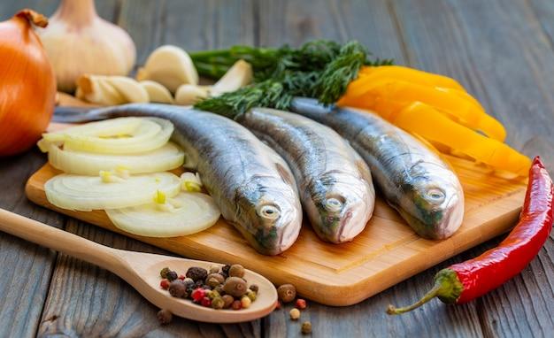 Les trois poissons truites avec poivrons, oignons et ail sur planche de bois