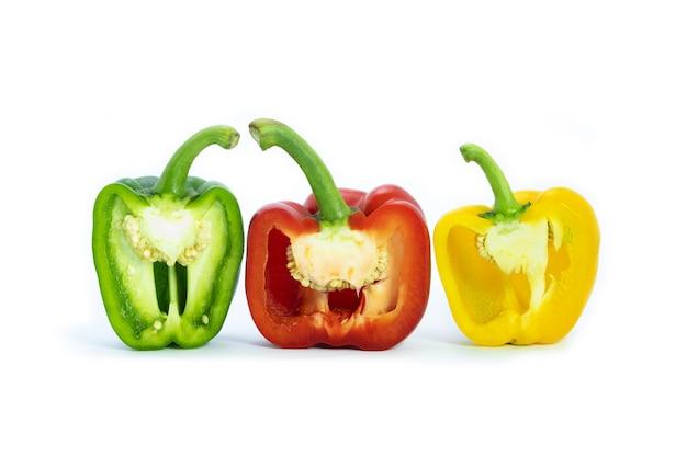 Trois poivrons coupés en deux. les poivrons sont rouges, verts et jaunes sur fond blanc. légumes colorés.
