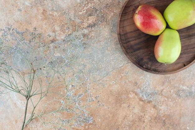Trois pommes fraîches avec fleur fanée sur planche de bois.