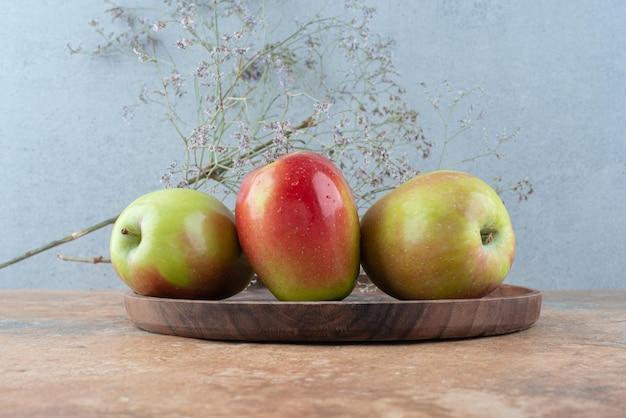 Trois pommes fraîches avec fleur fanée sur planche de bois