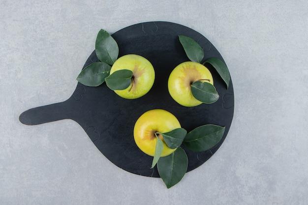 Trois pommes fraîches sur planche de bois noir.