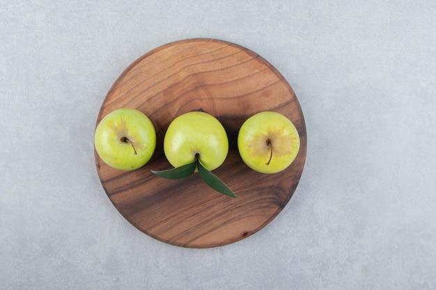 Trois pommes fraîches sur planche de bois.