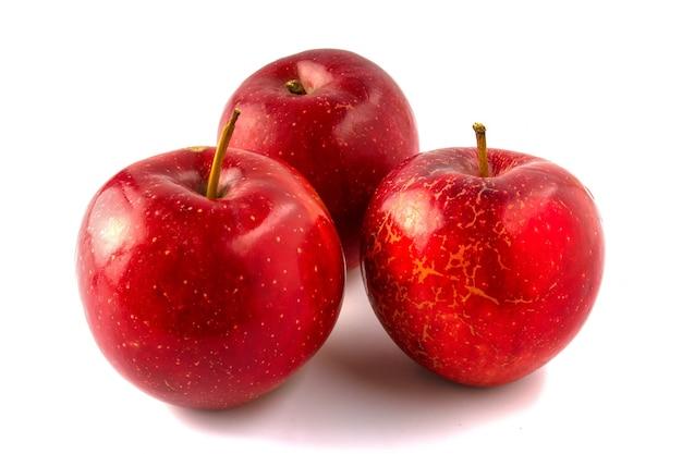Trois pommes rouges isolées sur fond blanc.