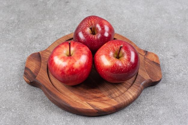 Trois pommes rouges sur planche de bois