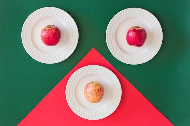 Trois pommes rouges sur des plaques blanches sur fond de papier rouge et vert, vue de dessus